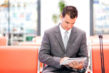 handsome businessman using tablet at airport photo
