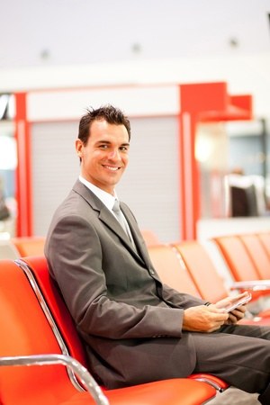 happy young businessman using tablet at airport  photo