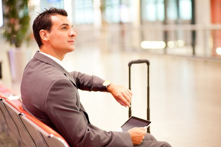 jetsetter: businessman checking time and using tablet at airport Stock Photo