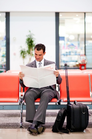 newspaper reading: young businessman reading newspaper at airport  Stock Photo