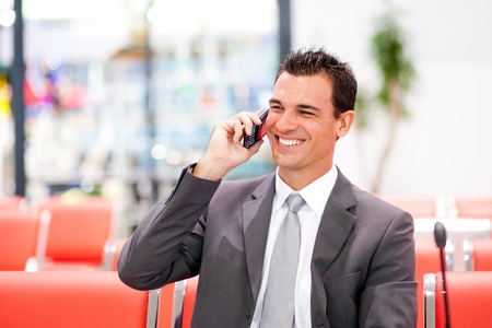 executive chair: happy businessman talking on cell phone at airport Stock Photo