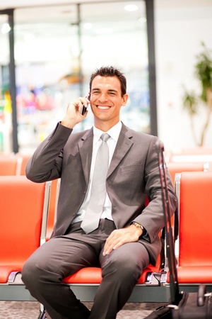 happy young businessman talking on mobile phone at airport photo