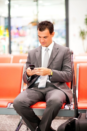 young businessman sending text messages at airport photo