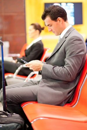 businessman sending or reading text messages at airport photo