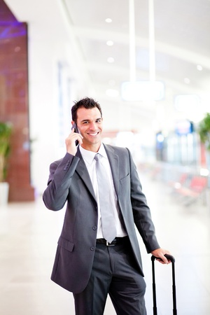 happy young businessman talking on cell phone at airport photo