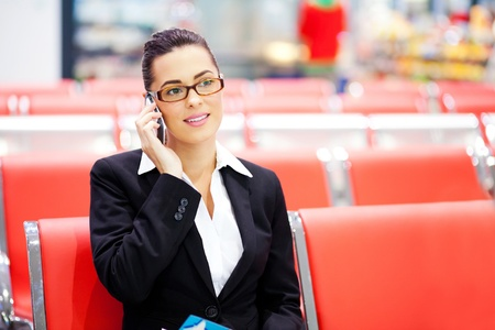 jetsetter: beautiful young businesswoman talking on cell phone at airport Stock Photo