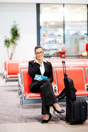 young businesswoman talking on cell phone at airport photo