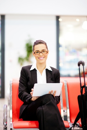 business traveller: young beautiful businesswoman using tablet at airport