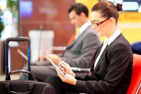 business travel: young businesswoman using tablet computer at airport while waiting for her flight