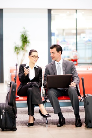 two business travellers waiting for flight at airport photo