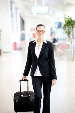 young beautiful businesswoman walking in airport with luggage photo