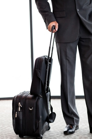 business traveller: businessman with luggage at airport Stock Photo