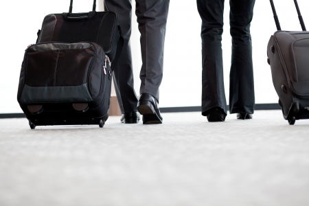 business travellers walking in airport with luggage