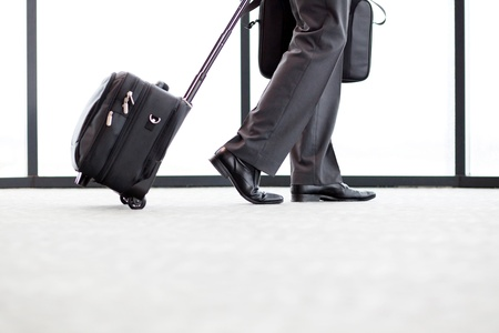 luggage airport: businessman walking in airport with his luggage Stock Photo