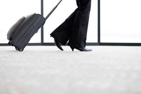 business traveller: businesswoman walking in airport with her luggage
