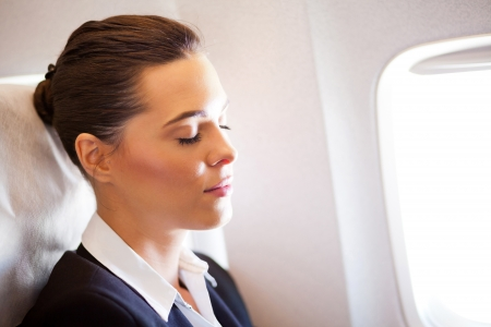 plane window: young beautiful businesswoman resting on airplane