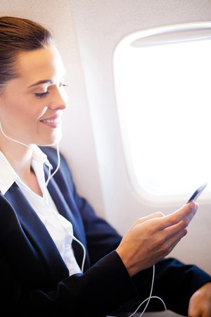 pretty businesswoman listening music on airplane photo