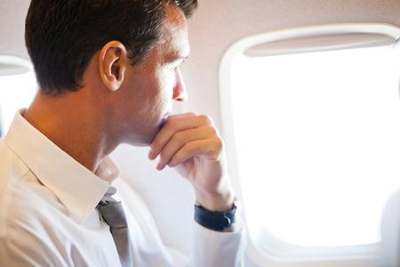 viajero: hombre de negocios reflexivo en el avi�n mirando hacia afuera Foto de archivo