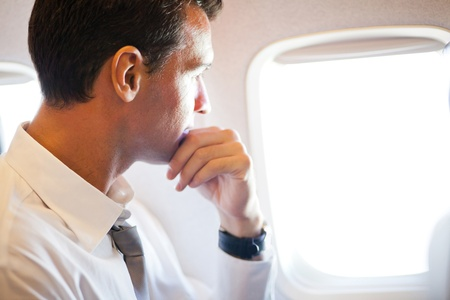thoughtful businessman on airplane looking outside photo