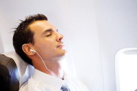 tired businessman listening music and relaxing on airplane photo