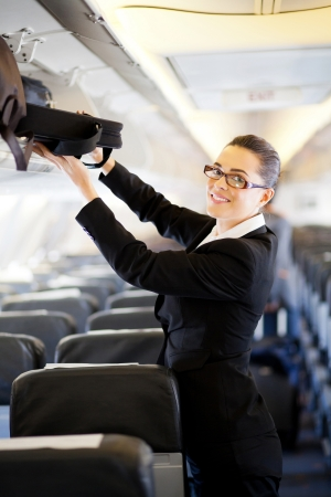 business travel: pretty businesswoman putting her luggage into overhead locker on airplane  Stock Photo