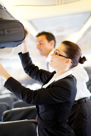 airline uniform: friendly flight attendant helping passenger with carry on luggage Stock Photo