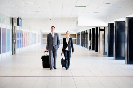 viajero: dos viajeros de negocios a pie en el aeropuerto