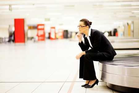 businesswoman sitting on conveyor belt and waiting for her luggage at airport   photo