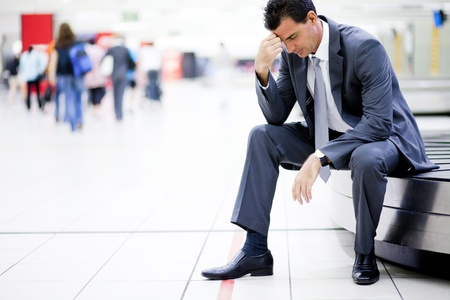 worried businessman lost his luggage at airport photo