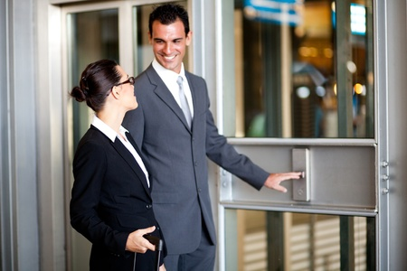 people in elevator: businessman and businesswoman using elevator at airport