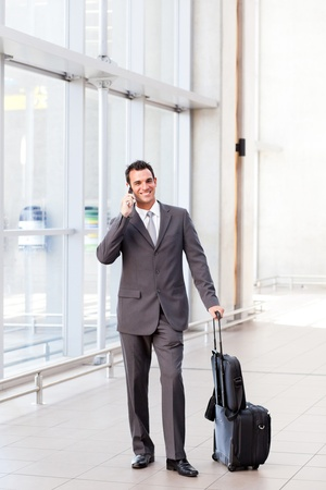 airport arrival: businessman talking on mobile phone at airport Stock Photo