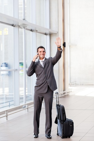 good bye: young businessman waving good bye at airport