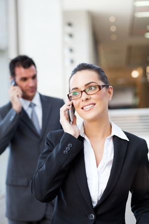 two businesspeople talking on mobile phone photo