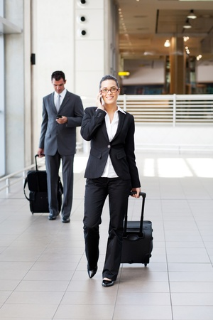 businesspeople walking in airport with luggage photo