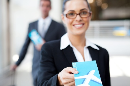 businesswoman handing over air ticket at check in counter photo
