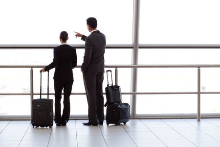 business traveler: silhouette of two businesspeople at airport  Stock Photo