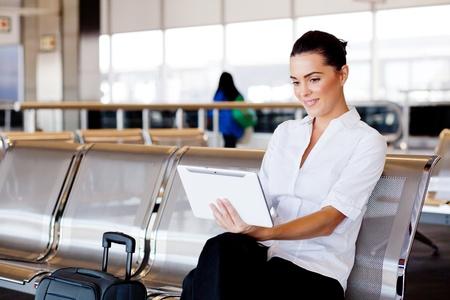 gente aeropuerto: empresaria joven y atractiva utilizando equipo Tablet PC en el aeropuerto Foto de archivo