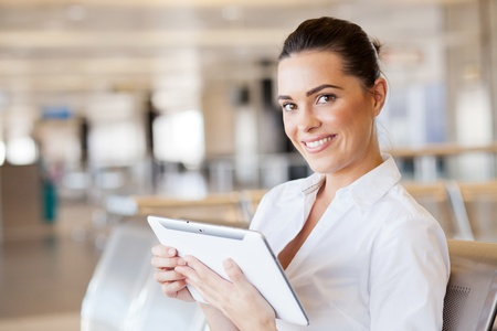 happy young woman using tablet computer at airport photo