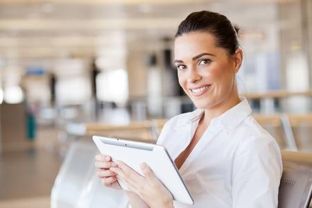 viajero: mujer joven feliz con Tablet PC en el aeropuerto