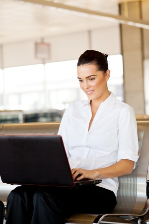 pretty businesswoman using laptop at airport photo