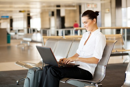 viajero: mujer joven utilizando equipo port�til en el aeropuerto Foto de archivo