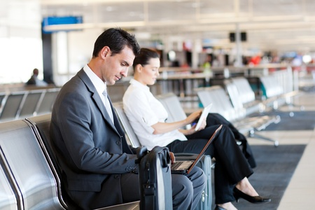 businessman and businesswoman using laptop and tablet computer at airport photo