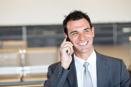 businessman phone: happy businessman talking on cell phone at airport Stock Photo