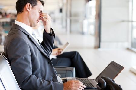 agotado: hombre de negocios cansado de tomar un descanso en el aeropuerto