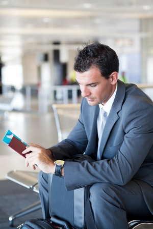 business travel: young businessman waiting for his flight in airport