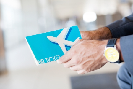 air ticket: man holding air ticket in airport
