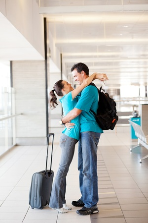 airport arrival: happy young couple reunion at airport Stock Photo