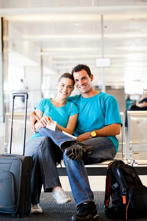 happy young couple waiting for flight at airport photo
