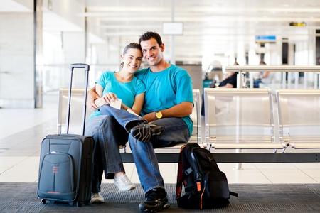 gente aeropuerto: amor pareja joven esperando para tomar el vuelo en el aeropuerto Foto de archivo
