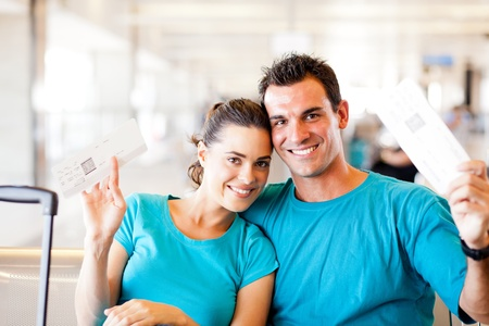 happy young couple with boarding pass at airport photo